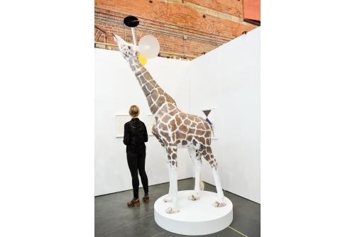 "Trevor Gould, A Trick of the Eye, 2014 Plywood, styrofoam, plaster, pigment, clay , epoxy, plexiglas Giraffe-mobile: 102""(h) x 24""(w) x 72""(l) Base: 7"" (h) x 48"" (diam.)"