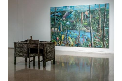 David Lafrance, Un atelier dans la forêt, 2018 Oil on canvas, sculpted wood, acrylic paint Painting 244 x 366 x 4 cm; desk 84 x 137 x 71 cm; chair 94 x  40,5 x 38 cm Collection of the Musée d'art contemporain de Montréal