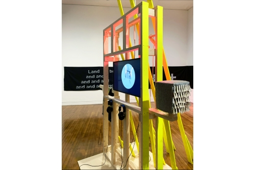 "Maria Hupfield, Electric Prop and Hum Freestyle Variations: National Gallery of Canada, 2017-2020 Wooden structure with hinged gate and side mount, 13 yellow wooden planks of various lengths, a selection of felt objects, a pink light fixture, the Territorial Acknowledgement banner"", a single channel video to be displayed on the monitor (performance with Ange Loft) Collection of the National Gallery of Canada"