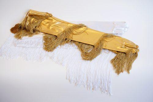Maria Hupfield Venice Fringe Gloves, 2015 Gants de soirée en soie blanche et dorée avec frange de 2 pieds et frange vénitienne dorée de 4 pieds White satin and gold colored evening gloves with 2' fringe and 4' venetian gold colored fringe. 30,5 x 13 x 2,5 cm (12'' x 4'' x 1'')