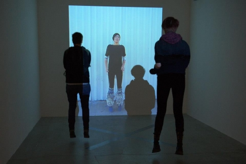 "Maria Hupfield Survival and Other Acts of Defiance, 2011 Video installation with silver ""X"" on floor made of aluminium tape Édition 3 2,4 x 1,2 x 1,2 x m (8' x 4' x 4')"